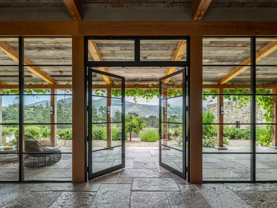 large glass doors opening to a covered stone patio
