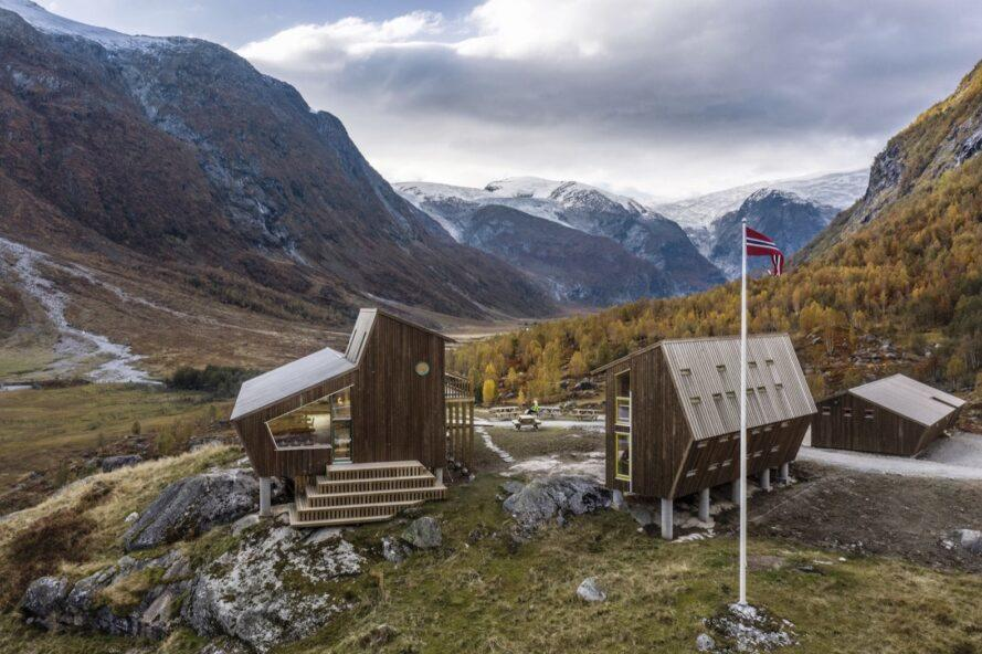 two angular wood cabins surrounded by mountains
