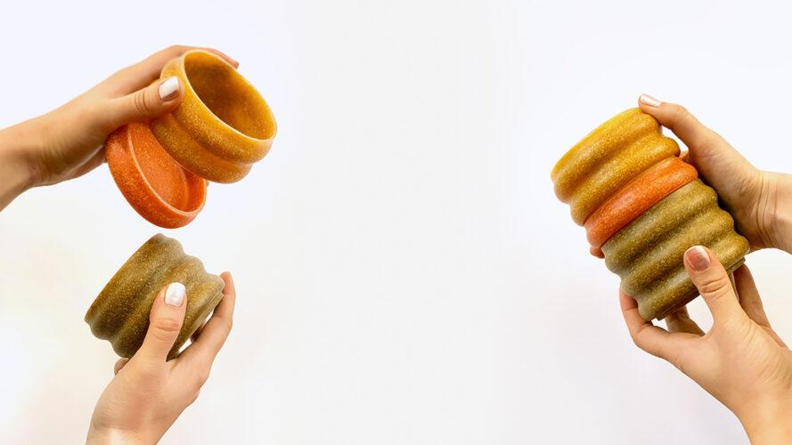 two sets on hands on the left and right, each holding mugs in various shades of orange