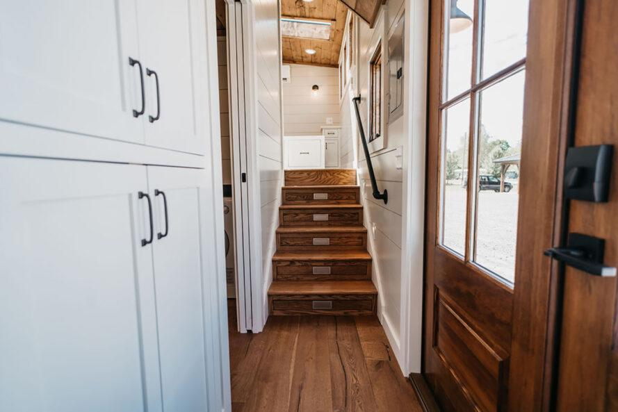 a white hallway with wood stairs