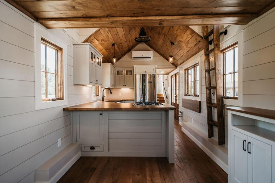 interior of a tiny home with white cabinets and wood ceilings and accents in the kitchen. a ladder is mounted on the wall