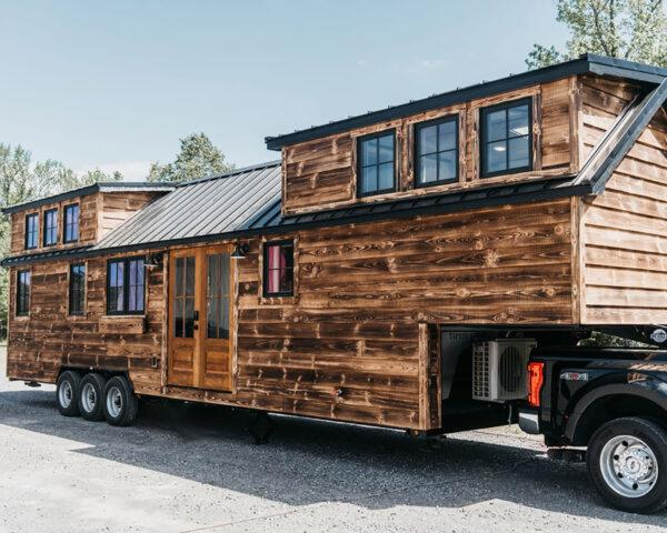 a tiny home on wheels with a wood, cabin-like exterior connected via trailer to a truck