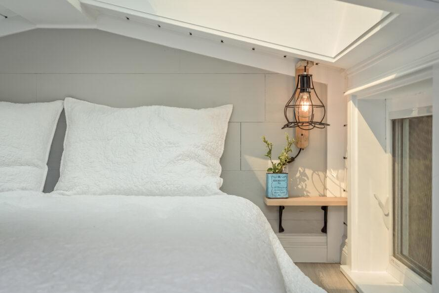 a white bedroom with unique light fixtures