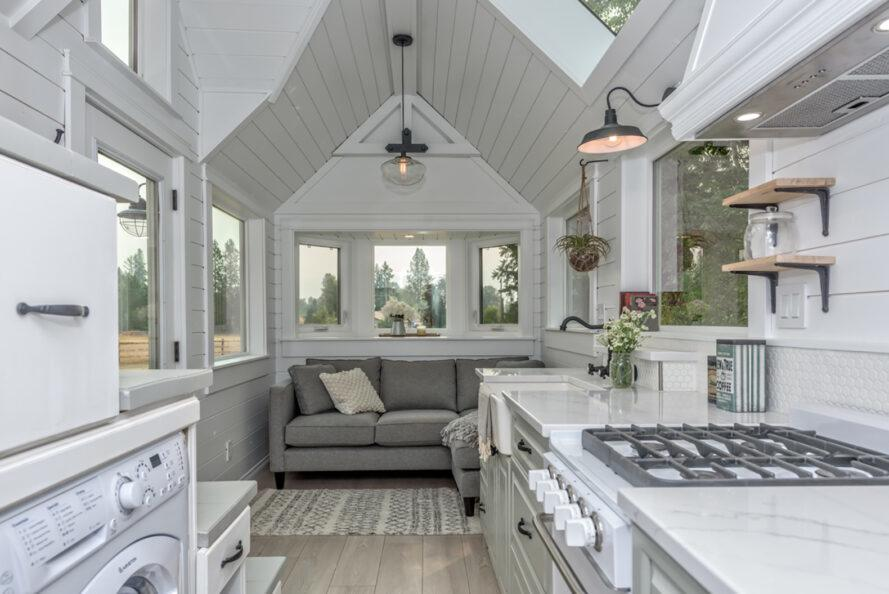 the interior of a tiny home featuring white shiplap walls, a sofa near a bay window and a kitchen