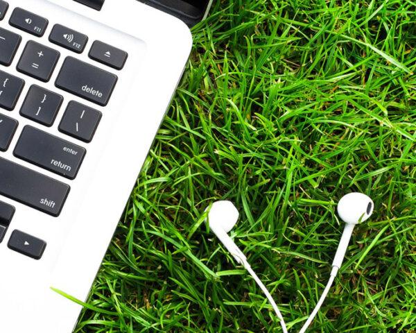 laptop and headphones in grass