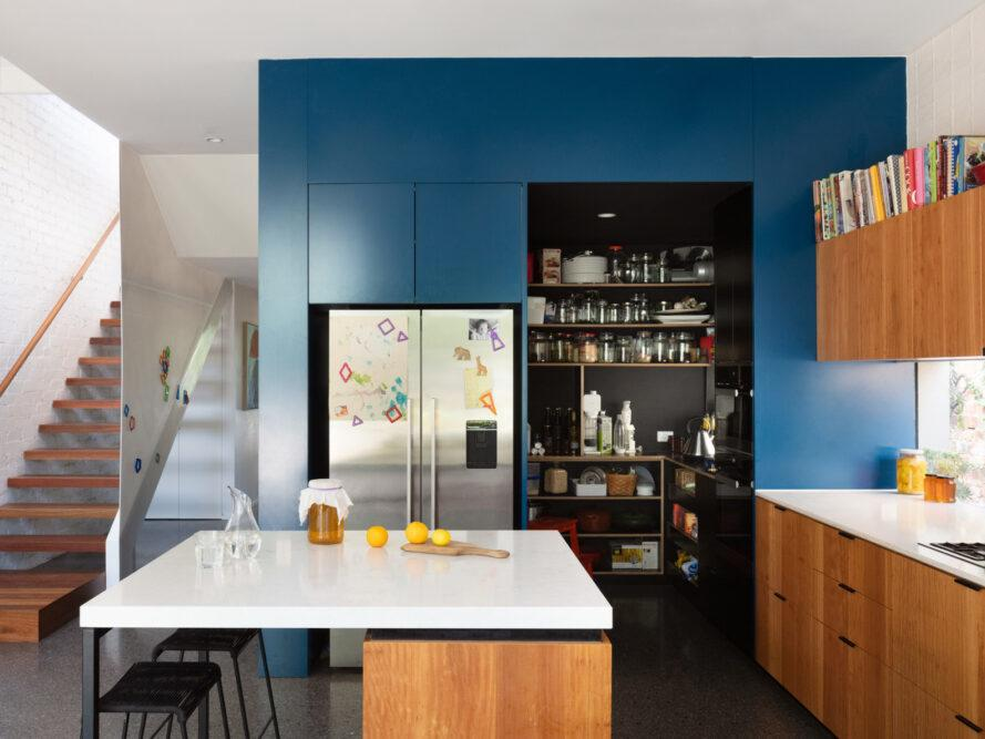 kitchen with blue wall, wood cabinets and white counters