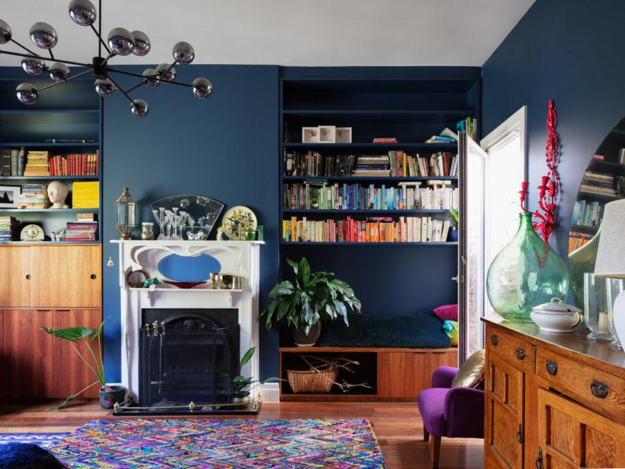 living room with navy walls, built-in bookshelves, small white fireplace and wood furniture