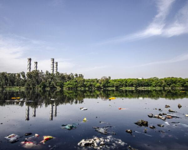 polluted lake with a factory in the background