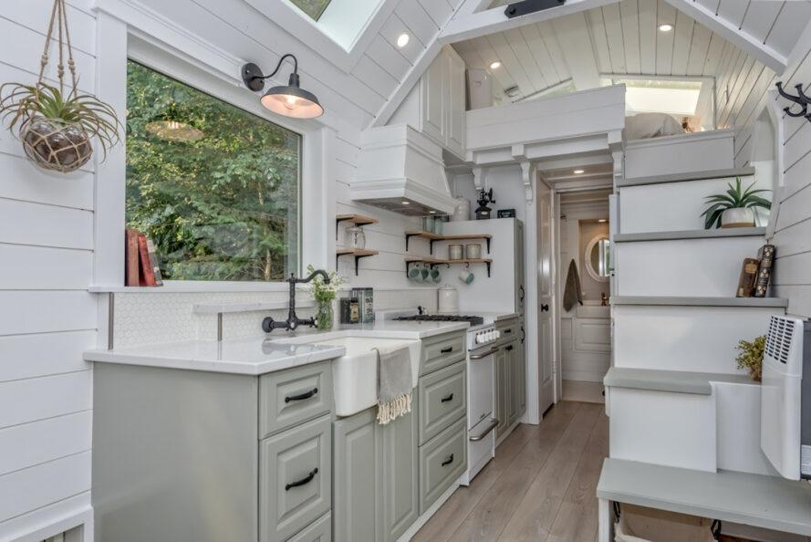 a kitchen inside the tiny home, featuring a large window above the sink