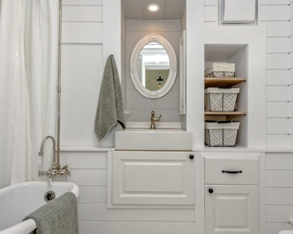 a white bathroom with a small mirror above the sink