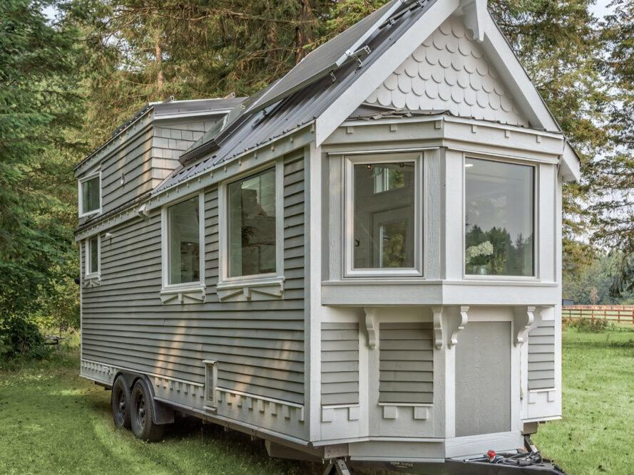 an off-white tiny home on wheels featuring solar panels on the roof and a bay window