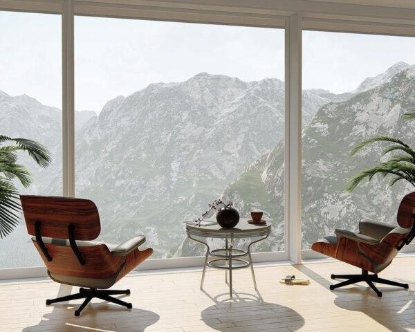 two chairs and two plants facing a glass window with mountainous views