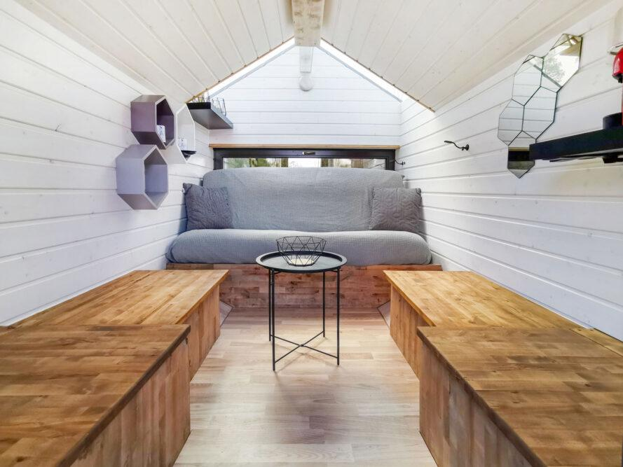 tiny cabin interior with white shiplap walls, wood benches and a gray sofa