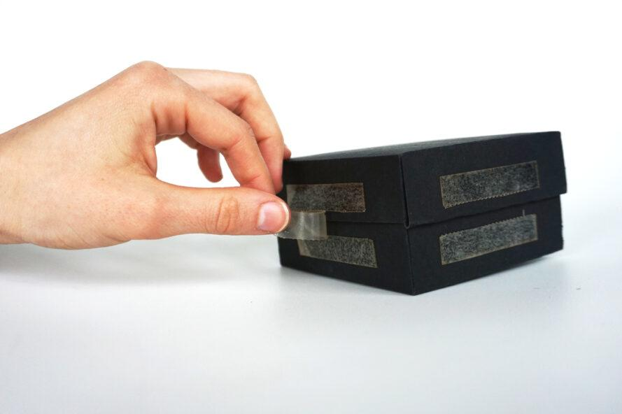 person applying bioplastic tape to a box