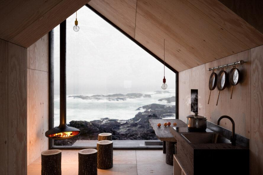 small cabin interior with one large wall of glass revealing mountain views