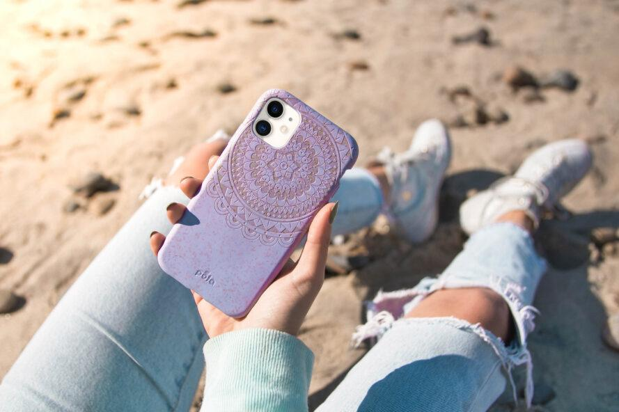 person on beach holding phone with light purple case
