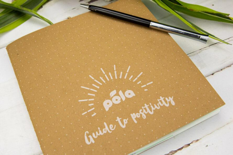 "small tan book that reads, ""Pela Guide to Positivity"""