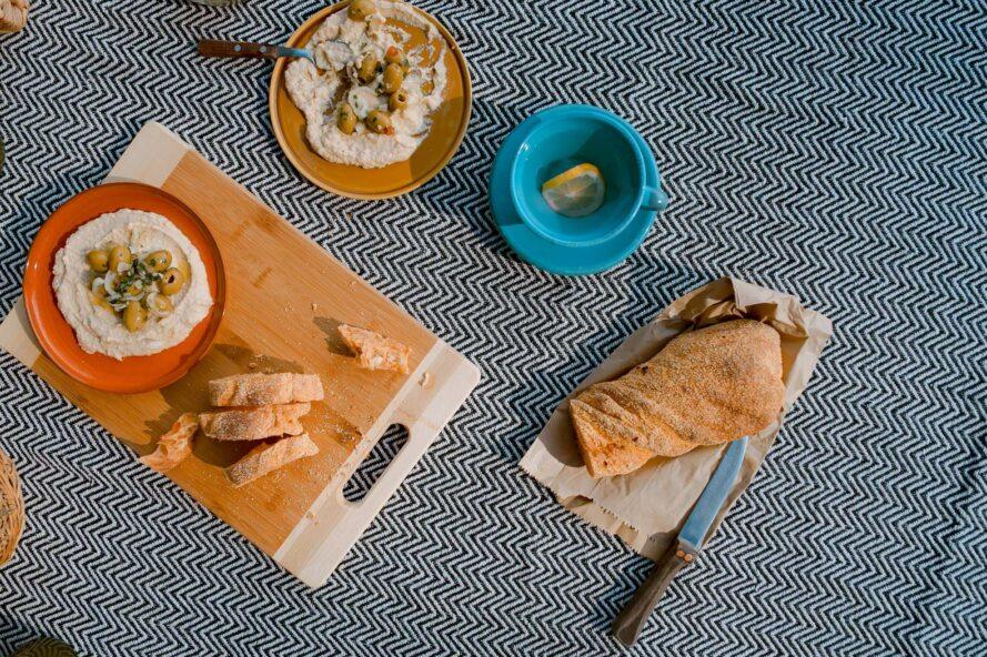 bowls of hummus, plate of bread and a wood cutting board on a blue and white blanket