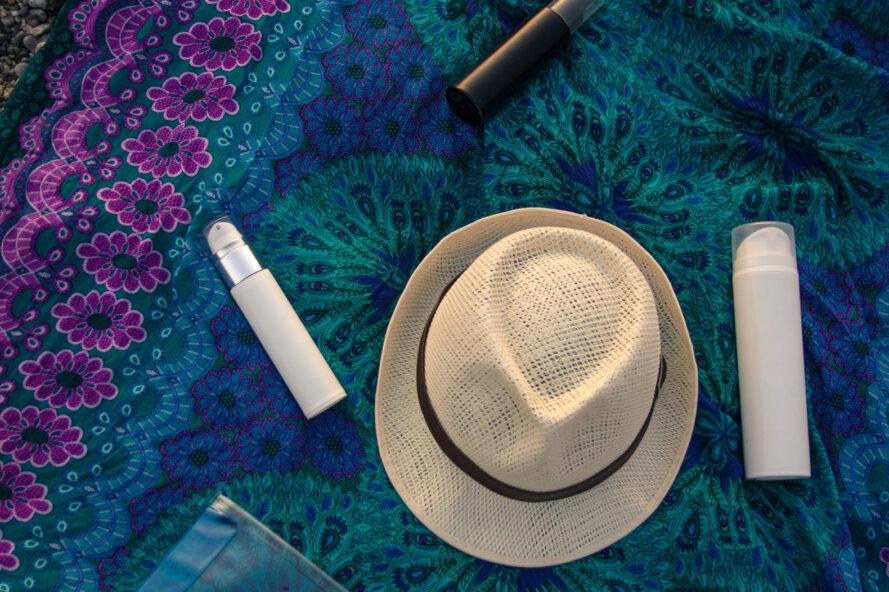 straw hat and three bottles of sunscreen and lotion on a purple and blue blanket