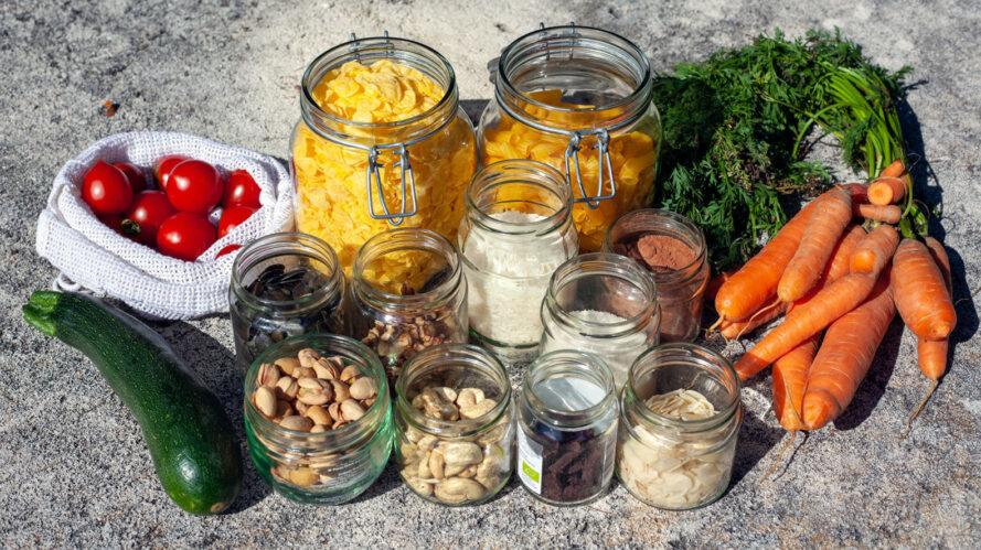 glass jars of nuts and pasta next to carrots, zucchini and tomatoes in a reusable produce bag
