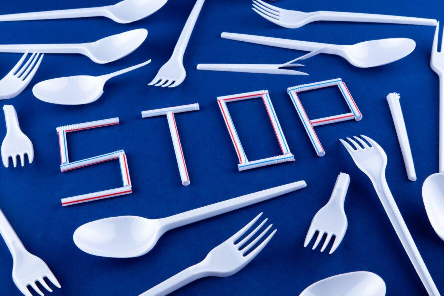 """plastic eating utensils surrounding plastic straws arranged to spell out the word """"STOP"""""""