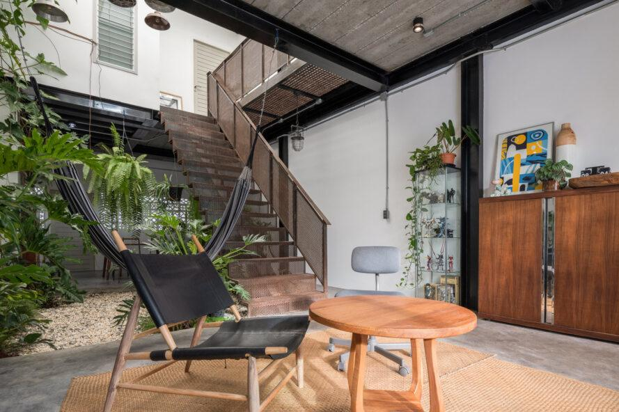 black chair and wood table in room near an indoor garden