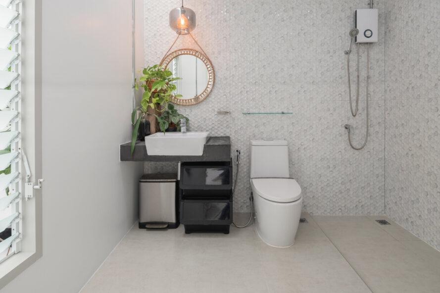 bright bathroom with white tiling and plants