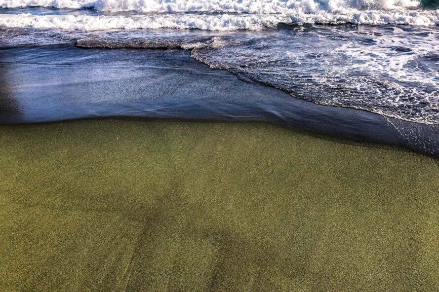 waves crashing on a beach with green sand