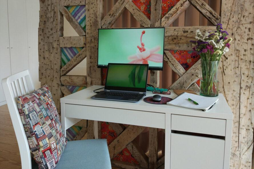 home office with laptop, desktop and vase of fresh flowers
