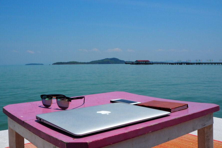 laptop on a pink table on a boat surrounded by ocean