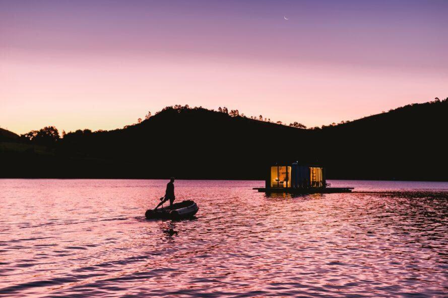 person canoeing toward small floating home at dusk