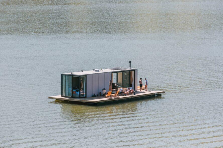 aerial view of gray home with deck floating on a lake