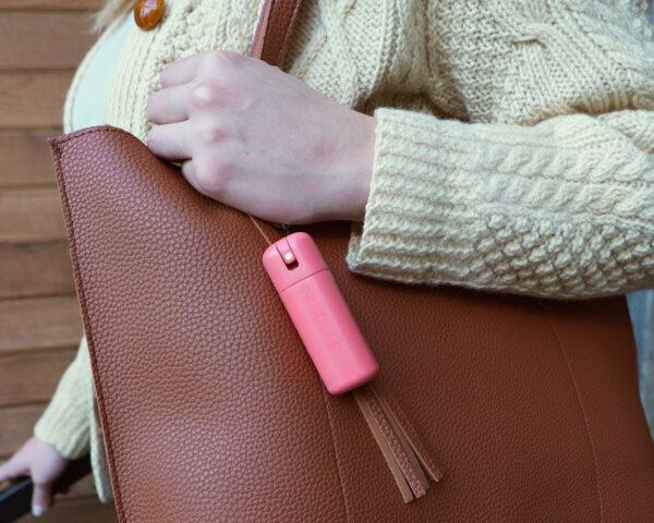 an arm in a white sweater clutching a brown purse with a pink bottle of sanitizer attached