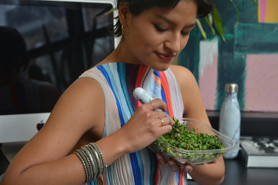 a person eating a salad with a fork.