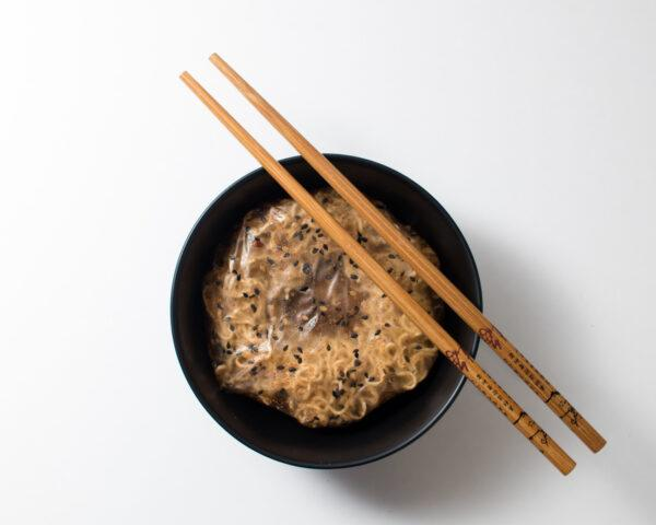 pack of instant noodles in a black bowl with wood chopsticks