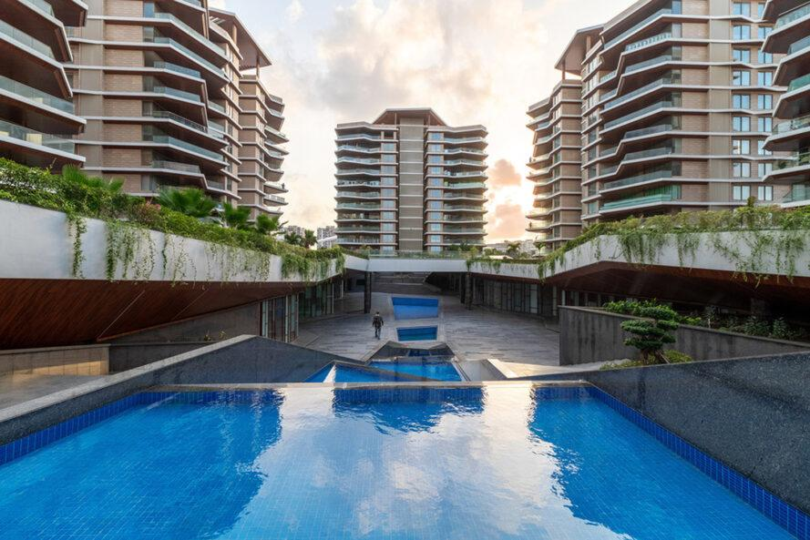 pool in the center of several apartment towers