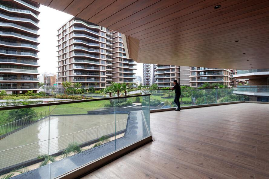 person looking out to green space from a covered wood balcony
