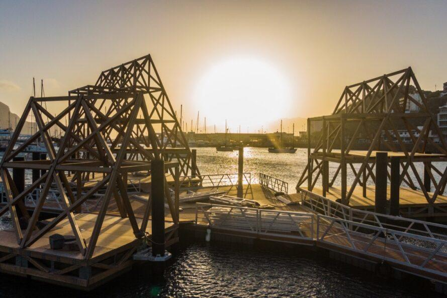 three pyramidal structures made from timber with sun setting in background