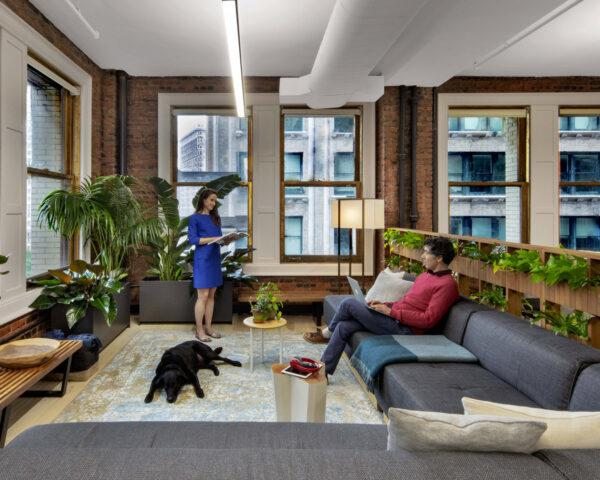 two people and a dog in lounge area with long gray sofa, brick walls and several plants