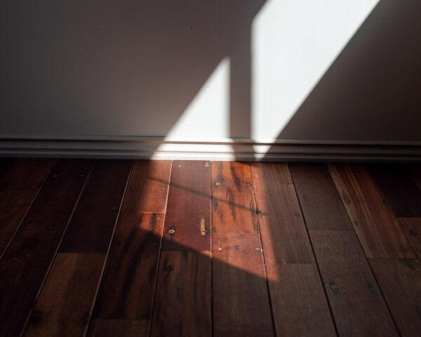 bright light and shadows against a white wall and dark wood floors