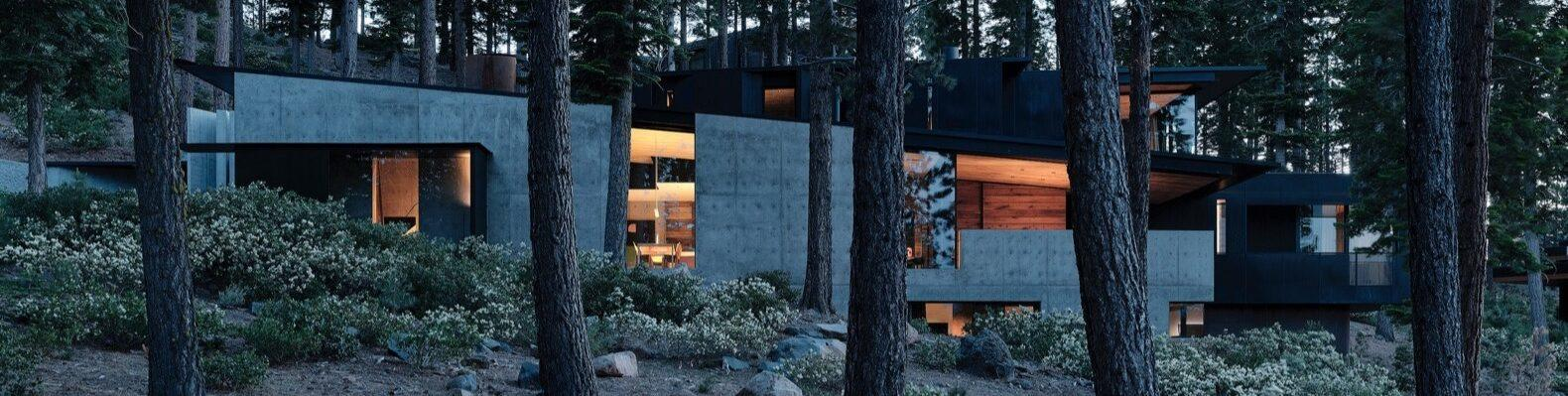 a home with a gray facade nestled within a slope in a forest. warm light shines from within the home.