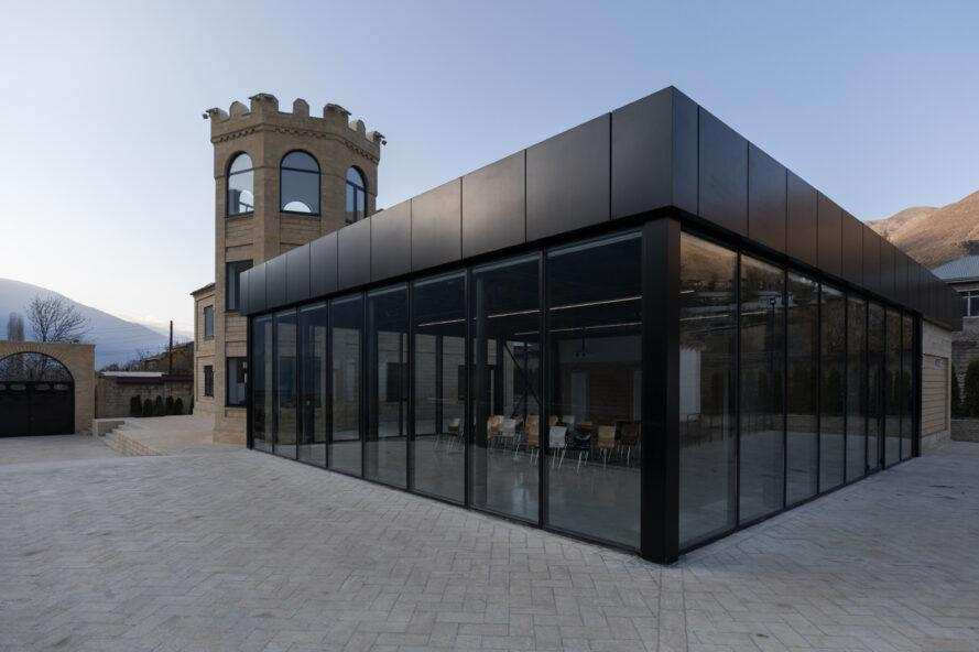 black metal building with full-height glass panels