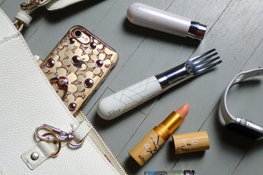 a flat lay with a silver fork with white, geometric patterned handle. the fork is surrounded by a phone, open lipstick and various other items.