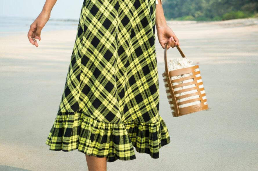 person in yellow and black plaid dress carrying brown vegan leather bucket purse