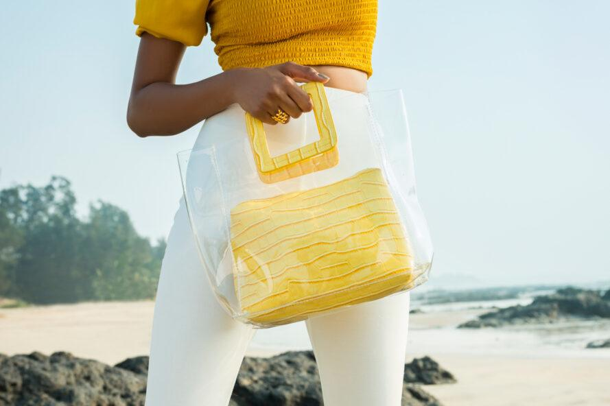 person with yellow top and white pants carrying a clear and yellow tote purse