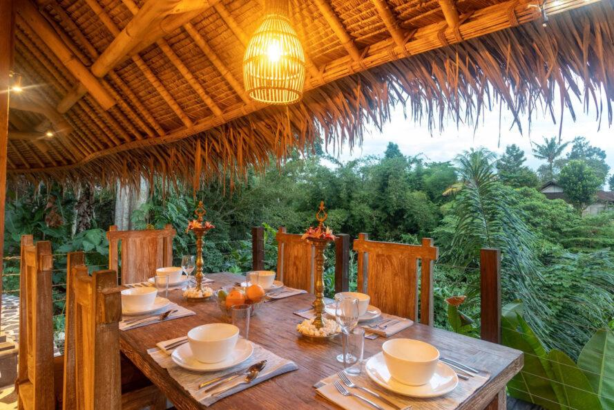 long wood dining table under thatched roof