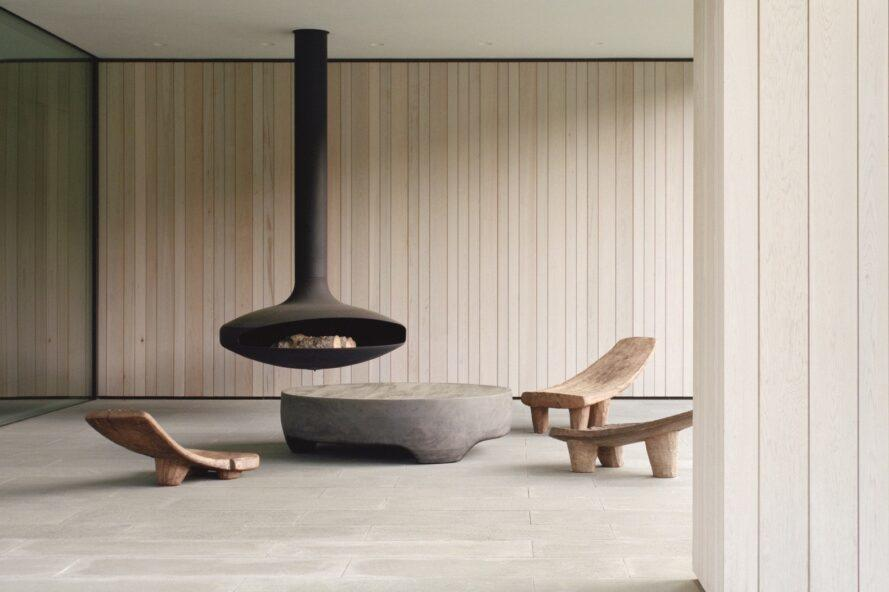 suspended fireplace with wood chairs surrounding it