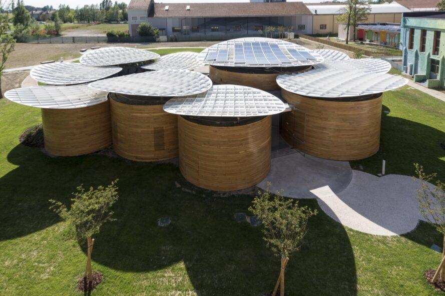 aerial view of connected round buildings with solar panels on the roofs