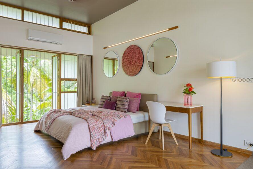large pink bed with three round mirrors on the wall