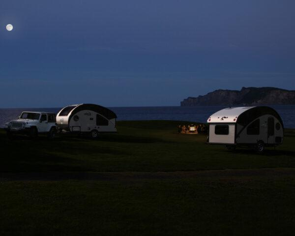 two small silver campers parked at night